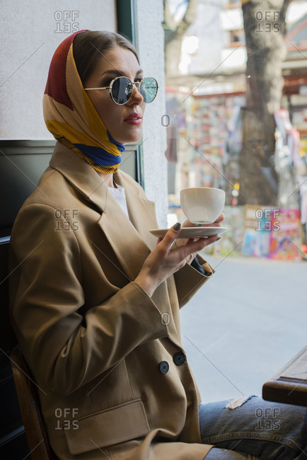 Side view of trendy young female in eyeglasses and shawl on head enjoying coffee while sitting with crossed legs in cafeteria near window in afternoon
