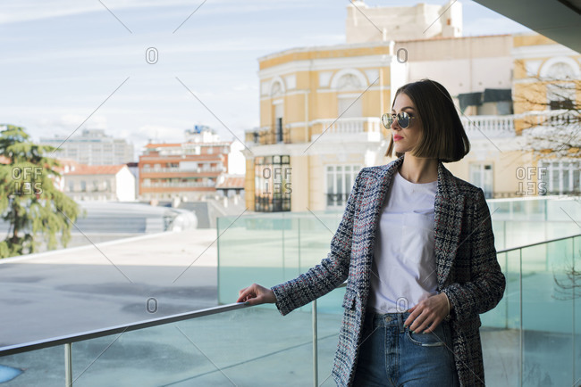 Thoughtful stylish young female in knitted jacket standing with sunglasses near transparent partition and street houses and looking away in afternoon