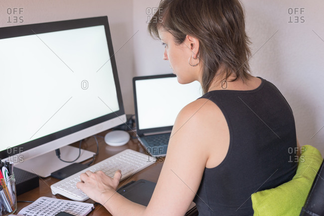 Rear view of a woman telecommuting from home with computers and white screens