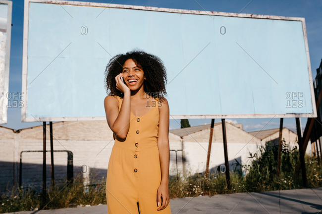 African American girl talking with cellphone standing alone against blank billboard in city