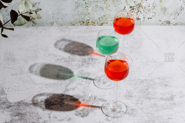 From above of glasses filled with colorful liquids put on concrete surface near plant with dark green leaves and rusty wall