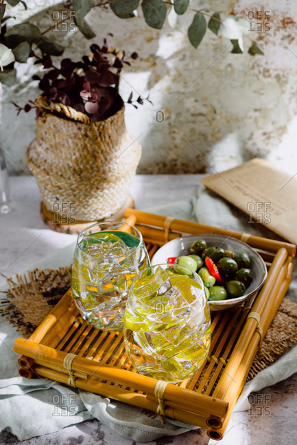 Large glasses of mojito cocktail with mint leaves and ice cubes put on concrete surface near plate with gherkins and vase with plant near shabby wall