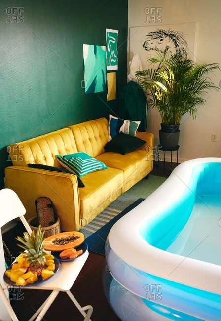 High angle of creative apartment with inflatable pool for home party and fresh tropical fruits placed on chair