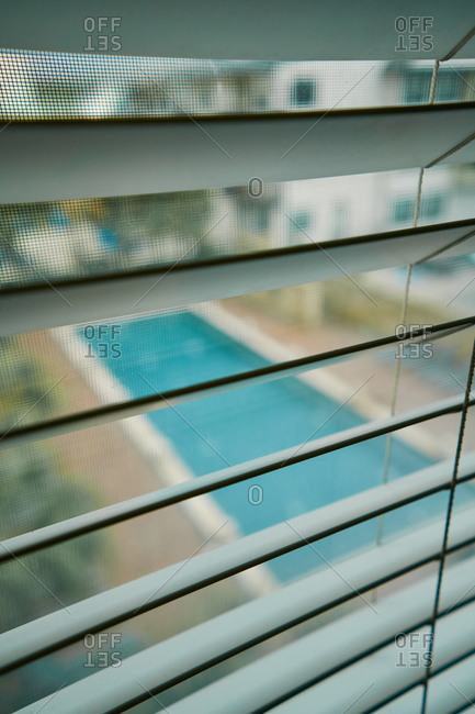 From above view of swimming pool in courtyard through metal jalousie and mosquito net on window