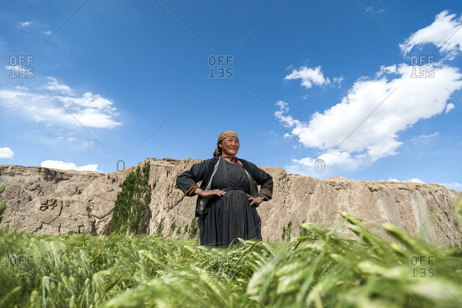 Lamayuru, India - July 4, 2011: A woman from Ladakh in the Himalayas proudly stands in a her wheat field