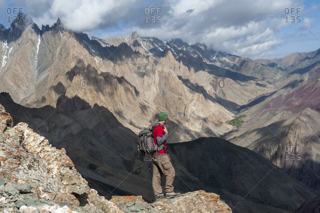 A trekker takes a break and admires the dramatic scenery from the top of the Dung Dung La during the Hidden valleys trek in Ladakh in India