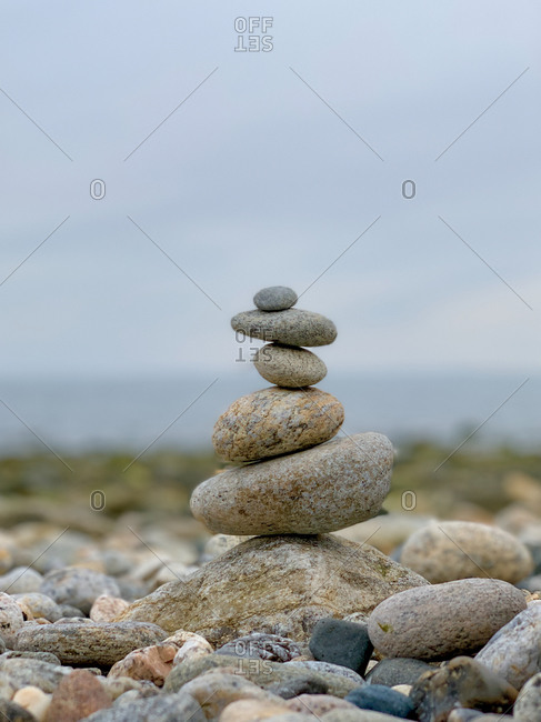Delicately placed rocks on top of each other near coastline creating a serene and calm effect
