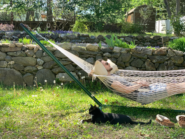 Young man enjoying sunshine while resting in a hammock in his backyard