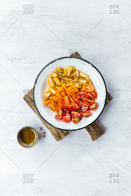 Yellow, orange and red cherry tomato slices in a plate on white background