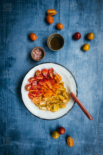 Yellow, orange and red cherry tomato slices in a plate on blue background