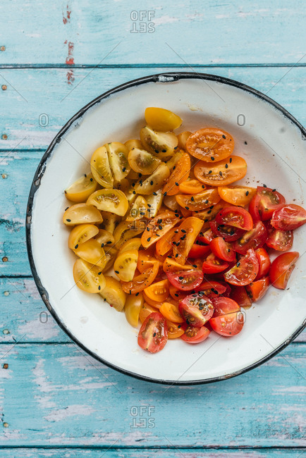 Slices of cherry tomato in red, yellow and orange shades in a plate