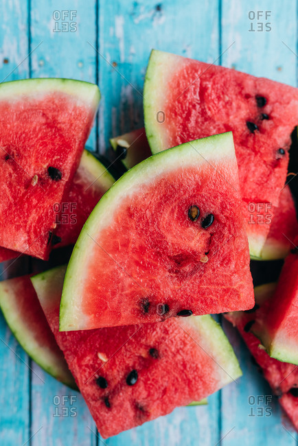 Sliced watermelon triangles in a pile on blue wooden background