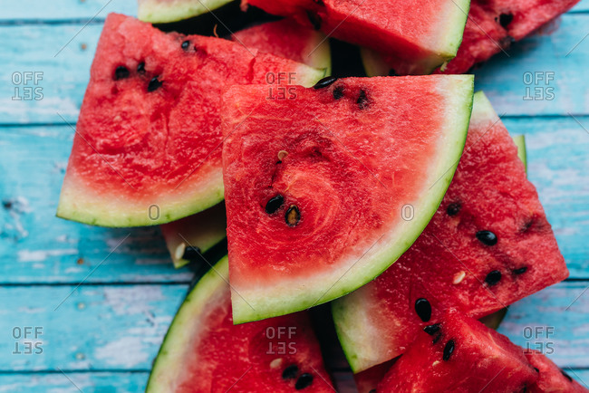 Sliced watermelon triangles in a stack on blue wooden background