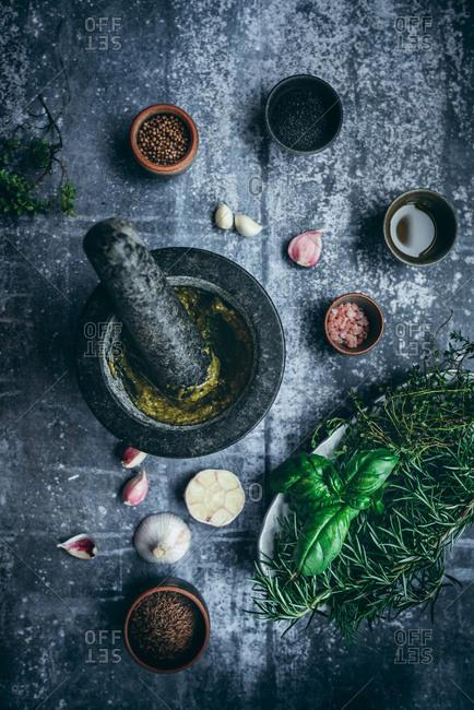 Homemade pesto basil sauce and ingredients on dark background