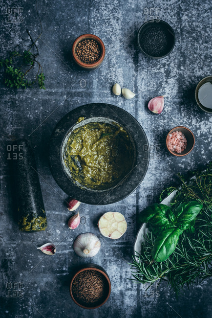 Mortar filled with homemade pesto basil sauce on dark background