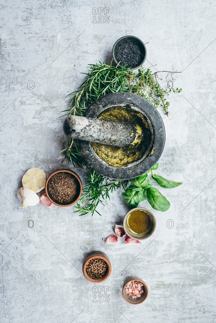 Making of fresh pesto basil sauce with a mortar and pestle on light background