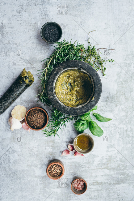 Fresh pesto basil sauce made with a mortar and pestle on light background