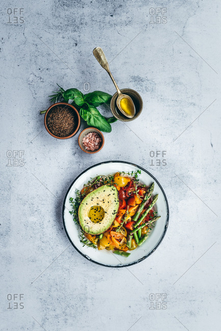 Healthy avocado salad with cherry tomato and asparagus on light background