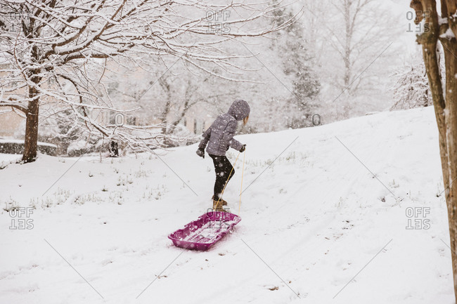 Girl dragging a sled up a snowy hill