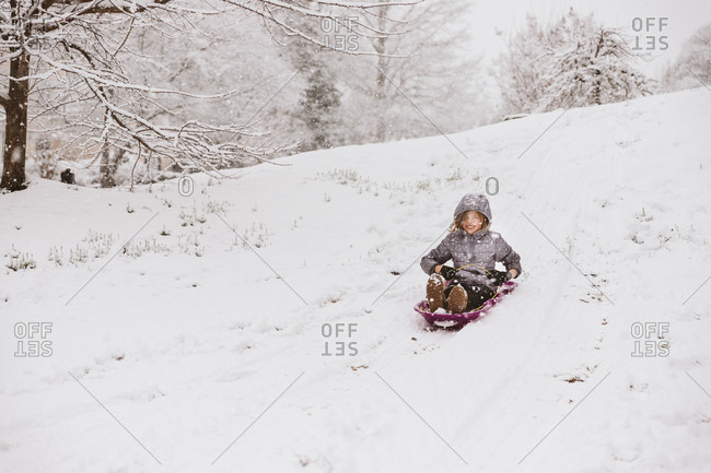 Girl riding a sled down a snowy hill