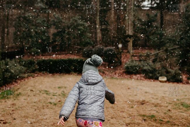 Rear view of girl running through snow fall