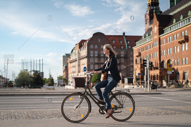 Blonde woman dressed in business casual clothing riding bike on city street
