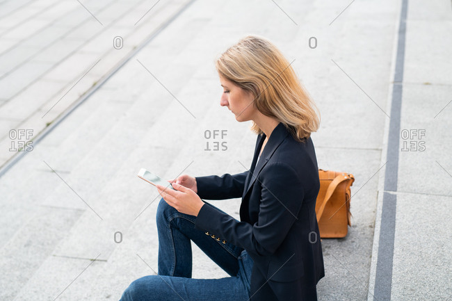 Blonde woman dressed in business casual clothing sitting on steps using cell phone