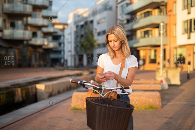 Blonde woman stopped and using cell phone while riding bike