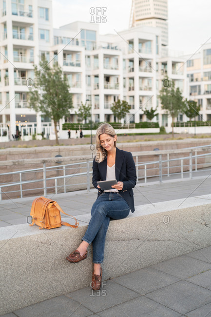 Blonde woman dressed in business casual clothing in urban setting using tablet