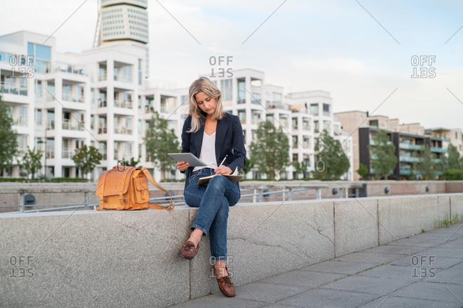 Woman dressed in business casual clothing in urban setting using tablet and taking notes