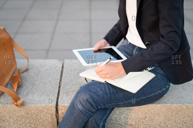 Close up of woman in urban setting using tablet and taking notes