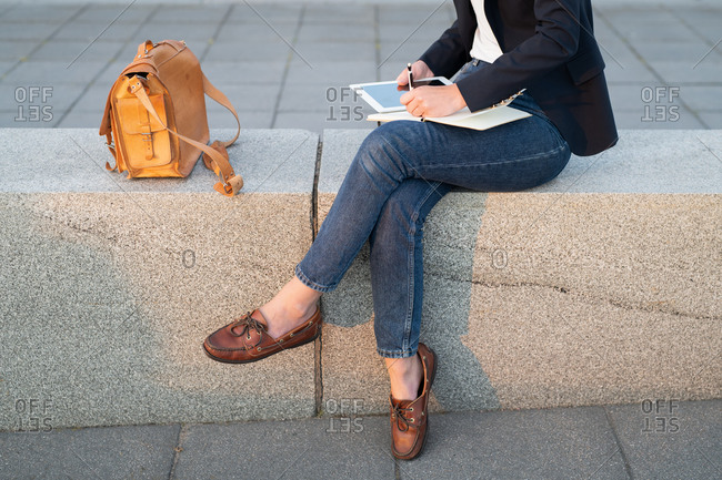 A woman in urban setting using tablet and taking notes