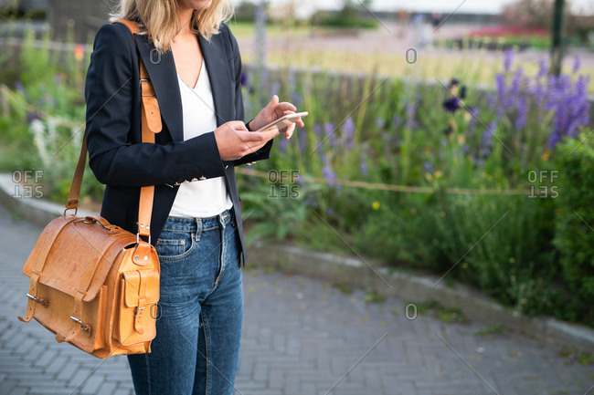 Woman dressed in business casual clothing walking in park and using cell phone