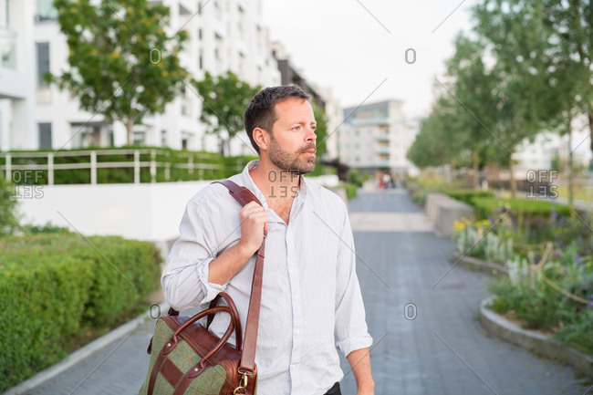 Man walking on city sidewalk carrying a briefcase bag