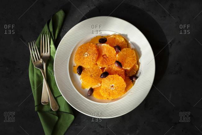Citrus salad on a white plate and dark background