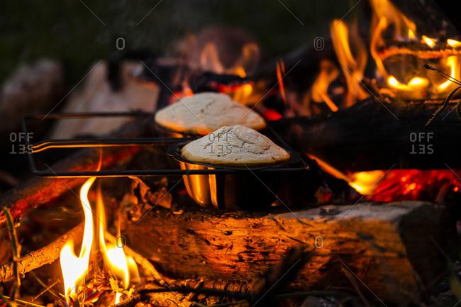 Johnnycake being prepared on a campfire