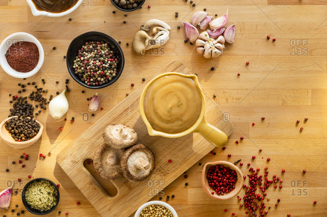 Gravy surrounded by ingredients on wooden surface