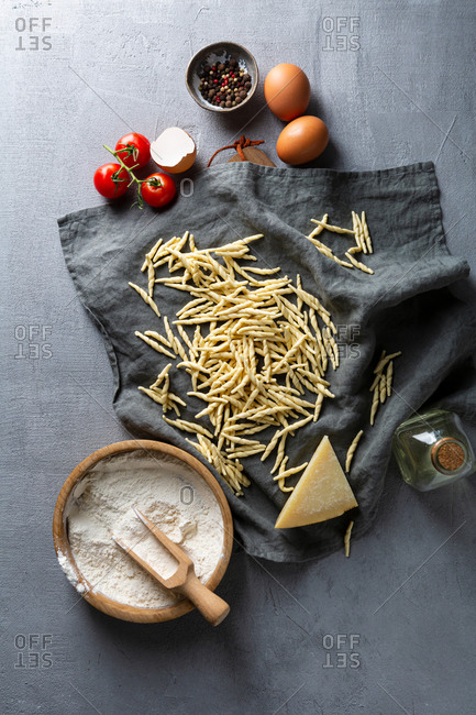 Overhead view of fresh pasta and flour on gray surface