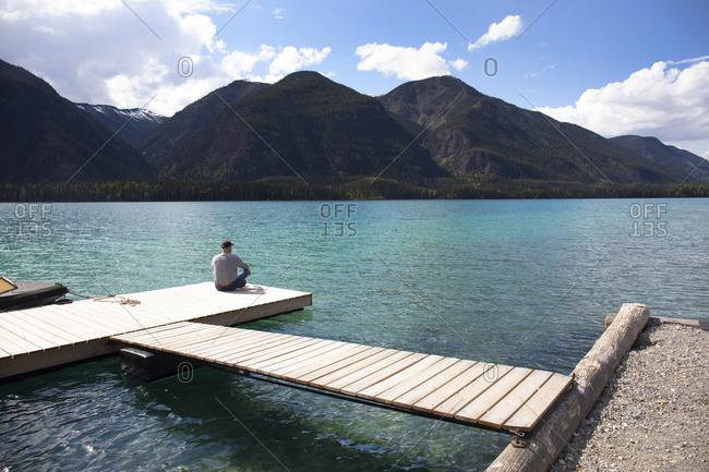 Man sitting on dock on Muncho lake, British Columbia, Canada