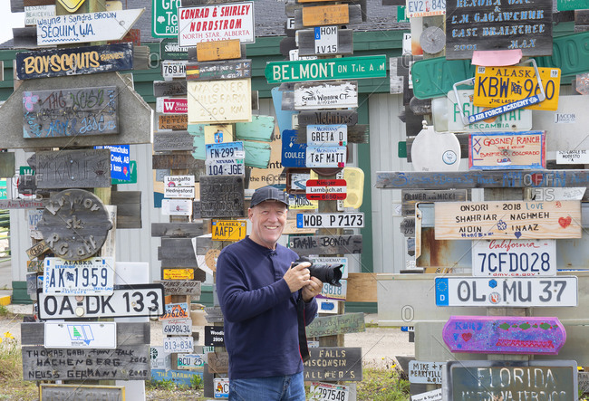 Watson Lake, Yukon, Canada - May 19, 2020: Tourist with camera at the Signpost Forest, an attraction of various signs tourist bring to hang up