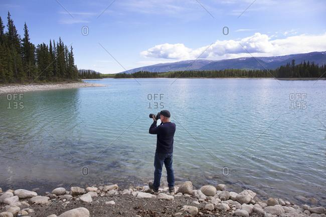 Tourist taking photographs at Dease Lake, British Columbia, Canada