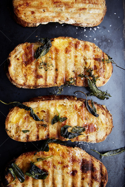 A row of grilled cheese sandwiches with crispy sage on a black roasting tray