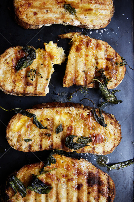 Grilled cheese sandwiches with crispy sage on a black roasting tray