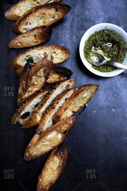 Slices of toasted bruschetta with green pesto on a dark background