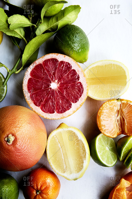 Close up of a variety of sliced citrus fruits on a white background