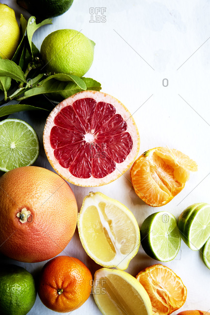 Close up of various sliced citrus fruits on a white background