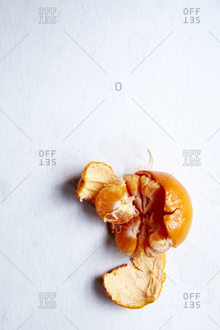 A half peeled citrus fruit on a white background