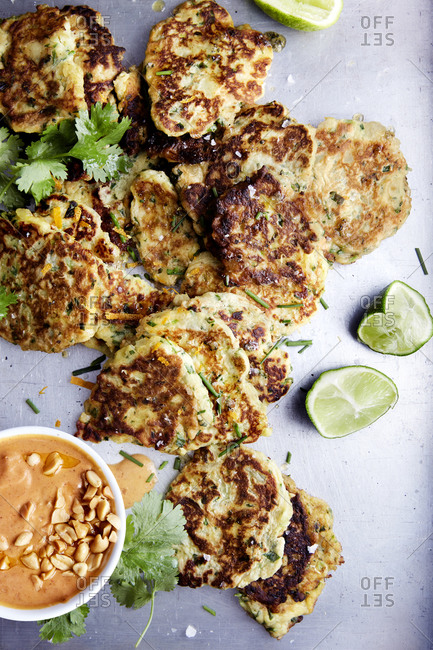 Sweet potato fritter with peanut sauce and fresh coriander and lime wedges