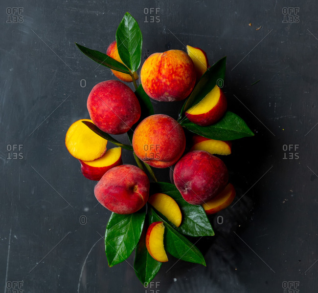 Group of peaches with leaves on a dark background
