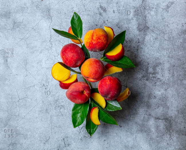 Group of peaches with leaves on a gray background